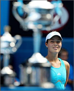Ana Ivanovic peeks at her runner-up trophy during a ceremony after her straight-set defeat to Maria Sharapova in the championship match.