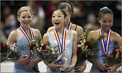 Mirai Nagasu, center, soaks in the moment with (from left) Rachael Flatt, Ashley Wagner and Caroline Zhang on the awards platform after their free skate routines.