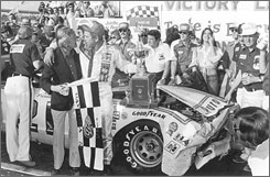 David Pearson stands alongside his crumpled car and the Daytona 500 trophy after a last-lap altercation with Richard Petty in the 1976 race.
