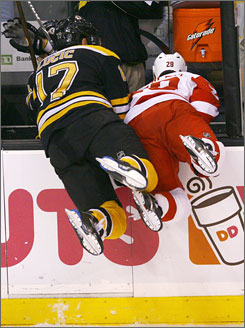 Hey boys, the ice is this way!!! Boston's Milan Lucic, left, joins Detroit's Brian Rafalski in heading over the boards in apparent search for a puck at TD Banknorth Garden, where the Red Wings beat the Bruins 3-1.