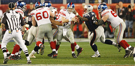 Giants quarterback Eli Manning eludes the Patriots' pass rush before completing a 32-yard strike to wideout David Tyree to sustain the game-winning drive.
