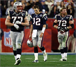 A dejected Tom Brady, center, is escorted to the sidelines by Patriot offensive tackles Nick Kaczur, 77, and Matt Light, 72, near the end of the fourth quarter. New England's offensive line could not give its QB the pass protection to which he had become accustomed.