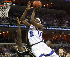 Memphis' Robert Dozier gets off a shot in the lane during the top-ranked Tigers' rout of Central Florida on Saturday.