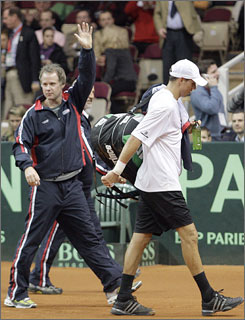 U.S. Davis Cup captain Patrick McEnroe waves to supporters as he leaves the court with team member Mike Bryan on Sunday in Vienna. Bryan withdrew with a hamstring injury in the second set against Stefan Koubek, giving Austria its only point.