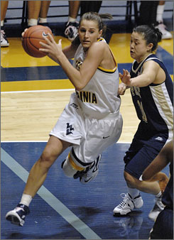 West Virginia's Meg Bulger drives around Pittsburgh's Karlye Lim as the Mountaineers held the Panthers to 20% shooting from the field.