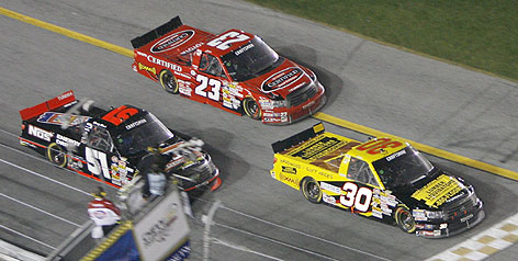 Craftsman Truck Series winner Todd Bodine hits the finish line first, just ahead of Kyle Busch's No. 51 and Johnny Benson's No. 23. The victory snapped Bodine's 34-race drought at Daytona.