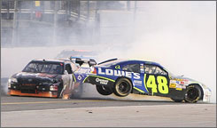 Jimmie Johnson's pole-winning car lifts after being struck by Denny Hamlin's Toyota during a late-race stack-up.
