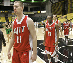 NJIT's Paulius Skema, left, walks off the court with teammates after they lost their final game of the season, finishing the year at 0-29.