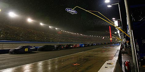 The Sprint Cup field sits under car covers on pit road at rainy California Speedway.