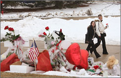 Two students pass by a memorial to slain students at Northern Illinois University on Monday, the first day of classes since a gunman killed five people. Tuesday, the school takes another step toward normalcy when the Huskies host Western Michigan in the first athletic event on campus since the shootings on Feb. 14.