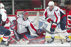 Cristobal Huet and Tom Poti, right, defend the goal during Washington's 4-0 victory over New Jersey. The game marked the Capitals debut for Huet, who made 18 saves.