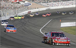 Carl Edwards leads Roush Fenway Racing teammate Matt Kenseth, Dale Earnhardt Jr., and a pack of others on the way to victory at Las Vegas.
