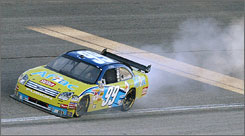 Carl Edwards' Ford leaves a trail of smoke as it expires near the end of Sunday's 500-miler.