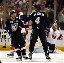 The Lightning's Vincent Lecavalier, right, celebrates his first-period goal with teammate Martin St. Louis in Tampa on Tuesday night. Lecavalier scored a hat trick in Tampa Bay's 8-4 victory over the New York Islanders.