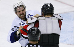Tampa Bay's Dan Boyle, left, and New Jersey's Zach Parise fight during a game last week. Columnist Ted Montgomery says the NHL's lack of tolerance for fighting has led to rough in-game play.