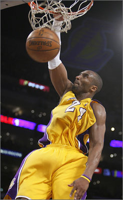 Kobe Bryant slams two of his 32 points against the Raptors in the Lakers' 117-108 victory at the Staples Center in Los Angeles.