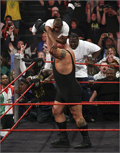 "Floyd Mayweather, top, is picked up and thrown outside the ring by Big Show after a weigh-in at ""Monday Night Raw"" on Monday in Milwaukee.  Mayweather injured his elbow but promised to be ready for Wrestlemania XXIV, to be held in Orlando on May 30."