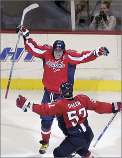 The Capitals'  Alex Ovechkin celebrates his third-period goal with teammate  Mike Green in Washington's 3-2 victory over Calgary. The goal was his league-leading 56th of the season.