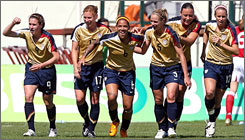 American team members celebrate with Natash Kai, center, after she scored the team's opening goal in its 2-1 win over Denmark in the Algarve Cup championship game.