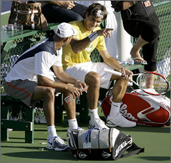 Switzerland's Roger Federer, right, talks with American James Blake as they work out together during the Pacific Life Open tennis tournament in Indian Wells, Calif., on Thursday.