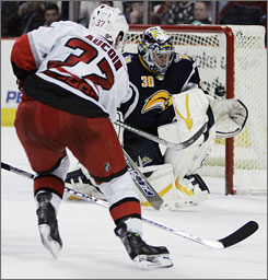 Sabres goalie Ryan Miller, right, stops a shot by Carolina's Keith Aucoin in the second period in Buffalo Friday night. The Sabres went on to rout the Hurricanes 7-1 to stay alive in the Eastern Conference playoff hunt.