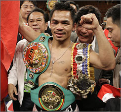 Manny Pacquiao poses with his WBC super featherweight title belt after beating Juan Manuel Marquez in a rematch four years in the making.