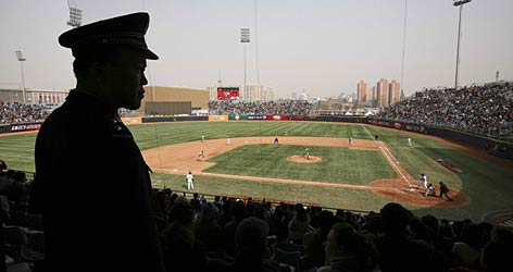A Chinese police officer keeps close watch over the second exhibition game between the Dodgers and Padres in Beijing.