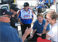 A.J. Foyt, left, talks with driver Darren Manning, right, and the rest of the ABC Supply crew during testing at Sebring International Raceway.