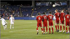 American Freddy Adu, left, watches his free kick fly over team Canada for his second goal of the night. The USA defeated Canada 3-0 in Nashville to clinch a berth in the Olympics. 