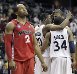 Georgia guard Sundiata Gaines, left, walks off the court as Xavier's C. J Anderson, Stanley Burrell and Josh Duncan celebrate their first-round victory.