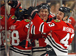 Patrick Kane, left, is mobbed by his Chicago teammates after he scored the winning goal in the Blackhawks' 4-3 overtime win over the St. Louis Blues on Sunday.