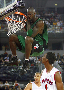 Celtics forward Kevin Garnett hangs from the rim after dunking over Raptors defender Chris Bosh during an exhibition game in Rome in October.  The game was a part of the NBA Europe Live tour.