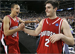 Stephen Curry, left, and Jason Richards celebrate Davidson's upset of Wisconsin. Curry scored 33 points and Richards made 13 assists without any turnovers in an impressive performance by the Wildcats.