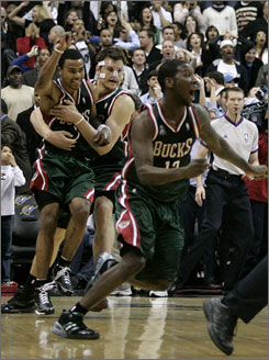 Bucks guard Ramon Sessions celebrates with teammates and receives a hug from center Andrew Bogut after sinking the game-winning jumper in Milwaukee's 110-109 win over the Wizards at the Verizon Center in Washington. Sessions' jumper foiled the return of Wizards guard Gilbert Arenas, who sat out 66 games due to a knee injury.