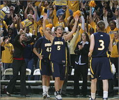 Erin Monfre (5) and her Marquette teammates erupt in jubilation as the Golden Eagles won the WNIT championship over Michigan State.