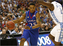 Kansas' Brandon Rush drives baseline past North Carolina's Marcus Ginyard during the first half of the Jayhawks' 84-66 victory in the NCAA tournament's semifinals. Kansas moves on to face Memphis for the national title on Monday night.