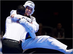 Diana Lopez jumps into the arms of her brother and coach Jean after winning the featherweight title bout at the Olympic Trials over Nia Abdallah.