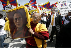 Thupten Donyo walks with a portrait of the Dalai Lama during Tuesday's Tibetan Freedom Rally in San Francisco.