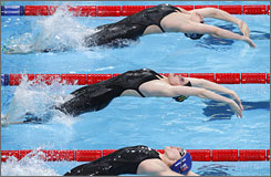 Zimbabwe's Kirsty Coventry, center, launches to start her world-record swim in the 200-meter backstroke at the World Short-Course Swimming Championships.