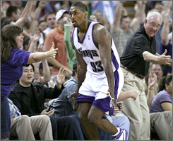 Sacramento's Ron Artest celebrates with fans after hitting one of his four three-pointers in the fourth quarter of the Kings' victory over the New Orleans Hornets.