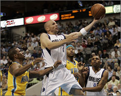 Mavericks guard Jason Kidd, center, drives to the basket past the Hornets' Chris Paul in Dallas. Kidd recorded his 100th career triple-double in Dallas' 111-98 victory.