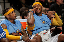 Nuggets teammates Allen Iverson, left, and Carmelo Anthony watch their game against Memphis from the bench in Denver. The Nuggets defeated the Grizzlies 120-111 and will meet the Lakers in the first round of the NBA playoffs.