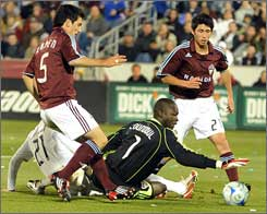 Colorado goalkeeper Bouna Coundoul stretches in front of defenders Facundo Erpen, left, and Kosuke Kimura.