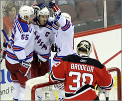 Christian Backman, left, and Martin Straka, right congratulate Rangers teammate Jaromir Jagr after a first-period goal as New York won all three road playoff games at the Prudential Center.