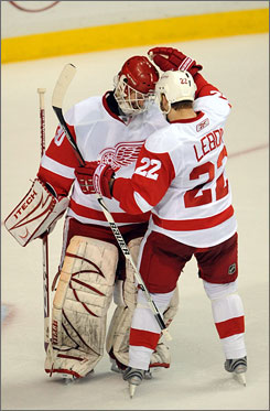 The Red Wings' Brett Lebda gives Chris Osgood a pat on the head after the goalie stopped all 20 Predators shots to help Detroit win the first-round series 4-2.