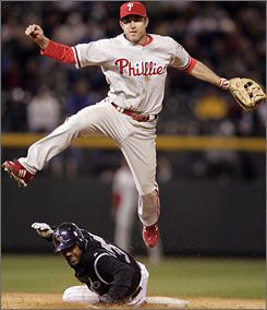 Philadelphia second baseman Chase Utley turns a double play during the sixth inning against Colorado. Utley hit a home run in his fifth straight game and leads the majors with nine.