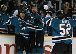 Sharks center Jeremy Roenick, left, celebrates with teammate Brian Campbell, center, and Craig Rivet after scoring a goal in the second period against the Flames in Game 7 of their first-round series. Roenick finished with two goals and two assists, as he helped lead San Jose to a 5-3 win over Calgary and an appearance in the second round of the Stanley Cup playoffs.