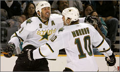 Stars center Mike Modano, left, celebrates with teammate Brenden Morrow after a late goal helped secure a Game 2 victory against the Sharks.
