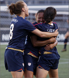 American players celebrate with Angela Hucles, center, who scored the game-winning goal during injury time in the team's 5-4 win over Australia on Saturday.