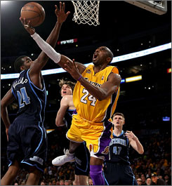 Lakers guard Kobe Bryant gets to the basket against the defense of Utah's Paul Millsap.